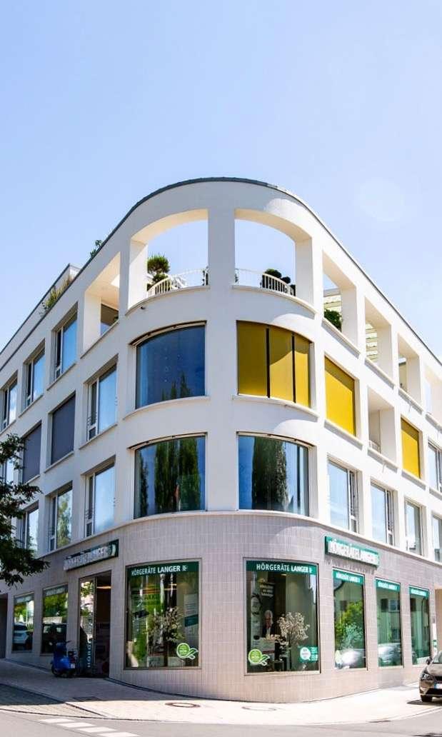 Schiffförmiges mehrstöckiges Wohn- und Geschäftsgebäude mit Schaufenstern und Stahlbeton bei strahlend blauem Himmel.